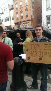"Kyle Moore holding his ""Legalize Marijuana"" sign at the weekly protest, while Jennie Stormes shook hands with Senator Cory Booker."
