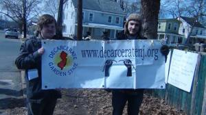 Kyle Moore (with hat) and Drew Howard holding the Decarcerate the Garden State banner.