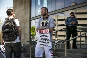 Kyle Moore (left) speaking with marijuana activist Dave Archer, with officer in background. Photo from NJ.com.